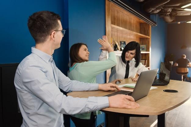 Grupa szczęśliwych ludzi biznesu i pracowników firmy w nowoczesnym biurze świętuje sukces, reprezentując firmę
