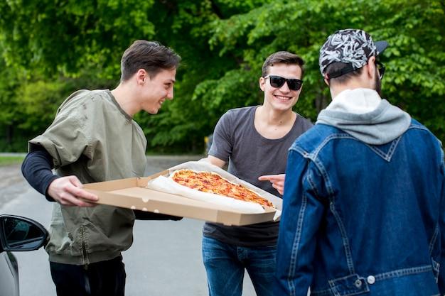 Grupa szczęśliwych ludzi idzie do jedzenia pizzy w przyrodzie