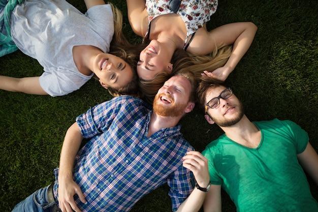 Grupa szczęśliwych ludzi leżących na trawie