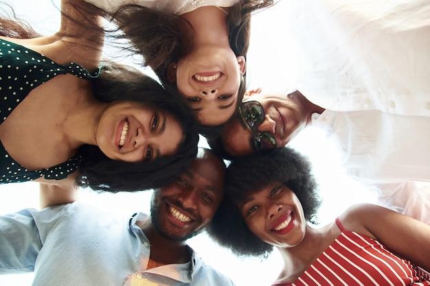 Grupa szczęśliwych ludzi międzynarodowych stojących i patrzących w dół na kamery