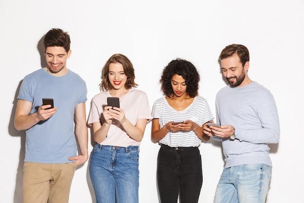 Grupa szczęśliwych ludzi wielorasowych korzystających z telefonów komórkowych