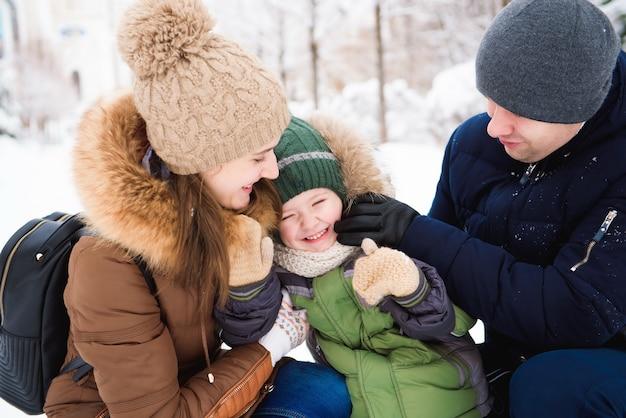 Grupa szczęśliwych mężczyzn i kobiet bawiących się i bawiących się śniegiem w zimowym lesie