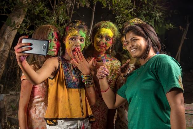 Grupa szczęśliwych młodych dziewcząt, zabawy i robienia selfie za pomocą smartfona na festiwalu holi. koncepcja festiwalu i technologii