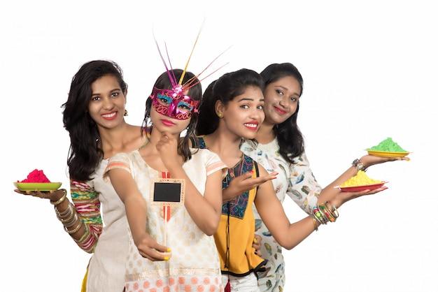 Grupa szczęśliwych młodych dziewcząt zabawy z kolorowym proszkiem na festiwalu kolorów holi