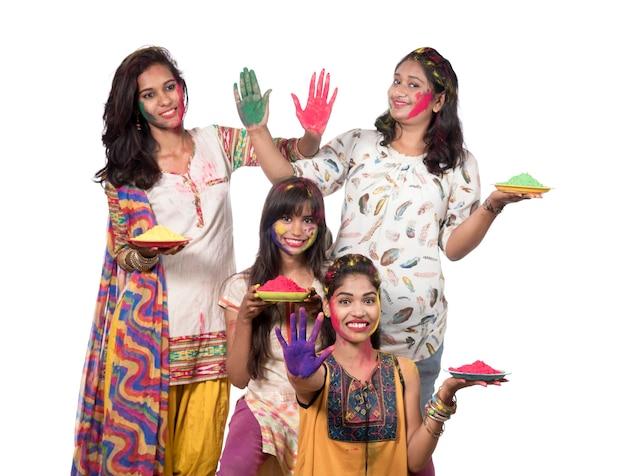 Grupa szczęśliwych młodych dziewcząt, zabawy z kolorowym proszkiem na festiwalu kolorów holi