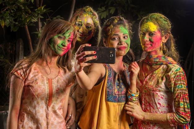 Grupa szczęśliwych młodych kobiet, zabawy i robienia selfie za pomocą smartfona na festiwalu holi. koncepcja festiwalu i technologii
