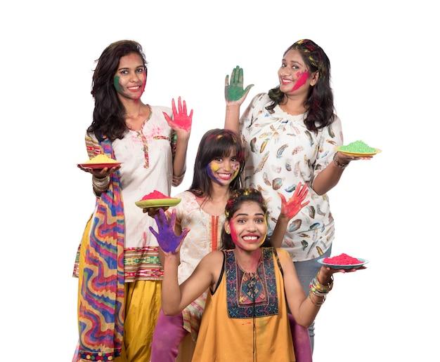 Grupa szczęśliwych młodych kobiet, zabawy z kolorowym proszkiem na festiwalu kolorów holi
