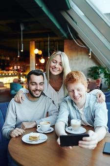 Grupa szczęśliwych młodych kochających przyjaciół robi selfie na smartfonie, pozując przy stole w kawiarni w weekend