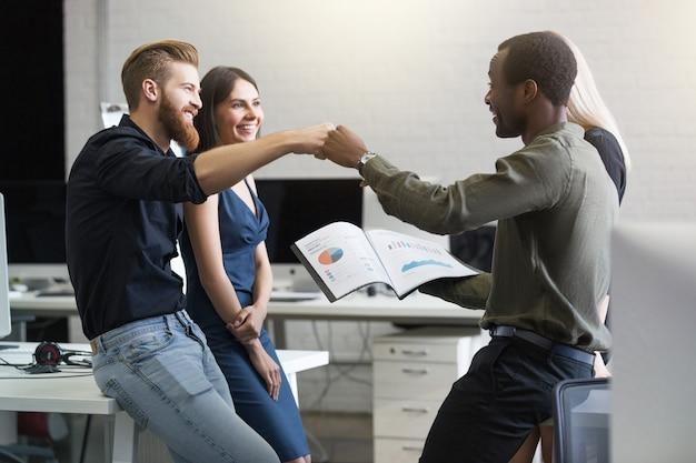 Grupa szczęśliwych młodych ludzi biznesu świętuje sukces