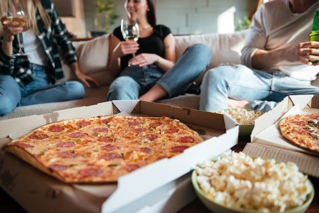 Grupa szczęśliwych młodych ludzi je pizzę, pije wino i piwo na kanapie w domu
