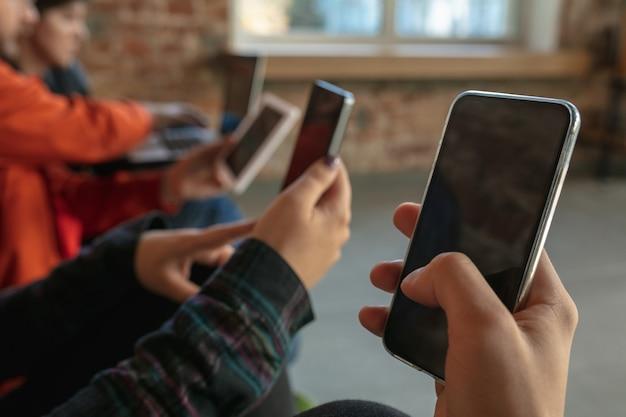 Grupa szczęśliwych młodych ludzi siedzi razem na kanapie. udostępnianie wiadomości, zdjęć lub filmów ze smartfonów, czytanie artykułów lub granie w gry i dobra zabawa. media społecznościowe, nowoczesne technologie.