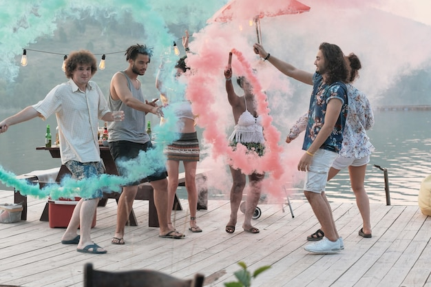 Grupa szczęśliwych młodych ludzi stojących na molo i zabawy podczas imprezy na świeżym powietrzu