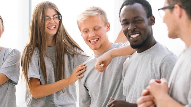 Grupa szczęśliwych młodych ludzi stojących w jasnym pokoju