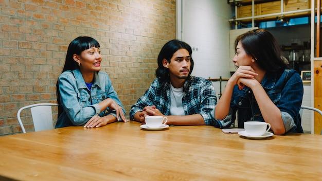 Grupa szczęśliwych młodych przyjaciół azji, świetnie się bawiąc i śmiejąc się, ciesząc się posiłkiem, siedząc razem w kawiarni restauracji.
