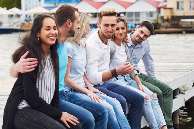 Grupa szczęśliwych młodych przyjaciół na molo, przyjemność z zabawy tworzy emocjonalne życie.
