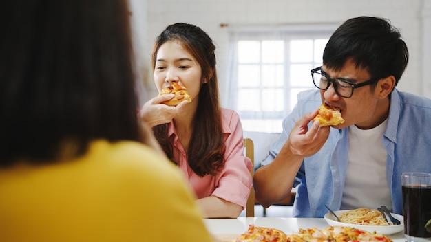 Grupa szczęśliwych młodych przyjaciół obiad w domu. azja rodzinne przyjęcie, jedzenie pizzy i śmiech, ciesząc się posiłkiem, siedząc razem przy stole w domu. świętowanie wakacji i wspólnoty.