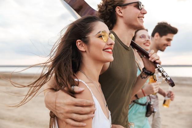 Grupa szczęśliwych młodych przyjaciół spacerujących po plaży, niosących gitarę, pijących piwo