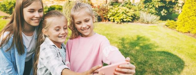Grupa szczęśliwych nastoletnich dziewcząt, śmiejąc się i biorąc selfie na telefon komórkowy na zewnątrz