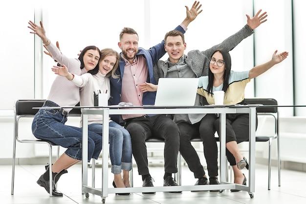 Grupa szczęśliwych pracowników siedzących przy biurku. zdjęcie z miejsca na kopię