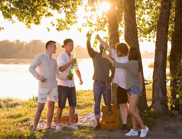 Grupa szczęśliwych przyjaciół brzęk butelek piwa podczas pikniku na plaży w promieniach słońca. styl życia, przyjaźń, zabawa, weekend i odpoczynek. wygląda wesoło, wesoło, świętująco, odświętnie.