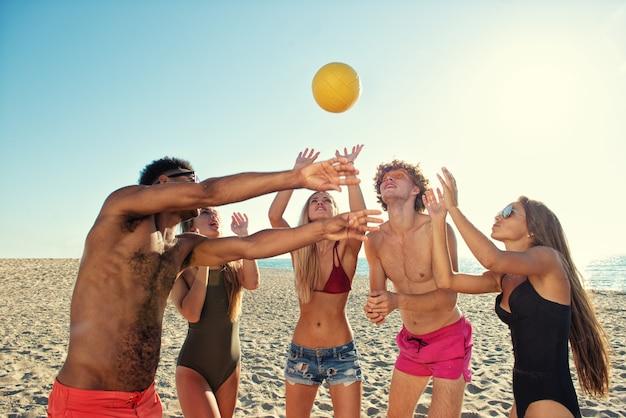 Grupa szczęśliwych przyjaciół grających w siatkówkę plażową na plaży