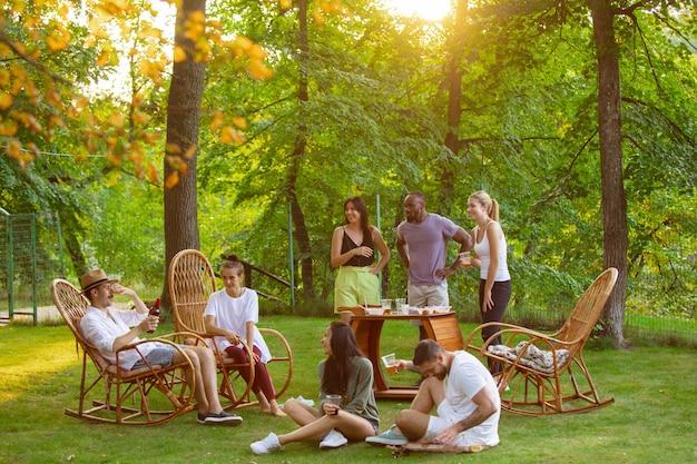 Grupa szczęśliwych przyjaciół jedzących i pijących piwo przy kolacji z grilla w czasie zachodu słońca