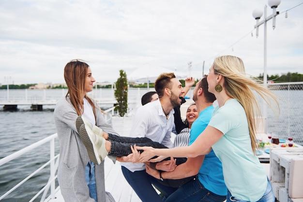 Grupa szczęśliwych przyjaciół na plaży, mężczyzna podrzucający szczęśliwą kobietę.