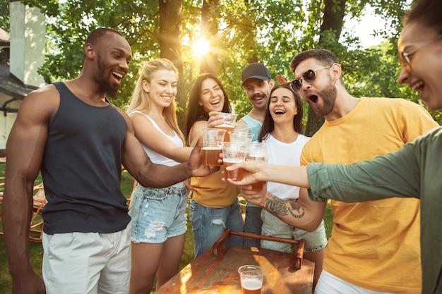 Grupa szczęśliwych przyjaciół o piwo i grill party w słoneczny dzień. odpoczynek razem na świeżym powietrzu na leśnej polanie lub podwórku