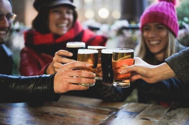 Grupa szczęśliwych przyjaciół, picia i opiekania piwa w restauracji z barem browaru