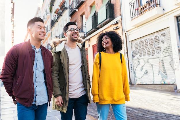 Grupa szczęśliwych przyjaciół spacerujących po ulicy. koncepcja przyjaźni.