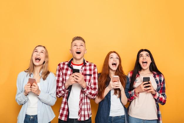 Grupa szczęśliwych przyjaciół szkoły posiadających telefony komórkowe