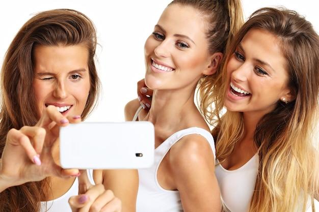 Grupa szczęśliwych przyjaciół w bieliźnie na białym tle robienia selfie