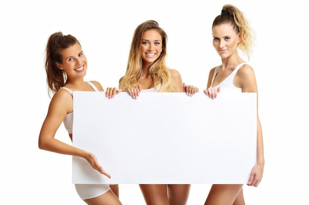 Grupa szczęśliwych przyjaciół w bieliźnie na białym tle z banerem