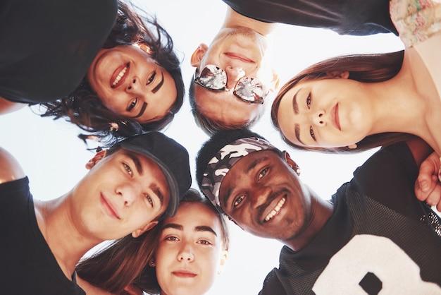 Grupa szczęśliwych przyjaciół w kręgu zdjęć poniżej.