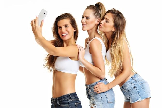 Grupa szczęśliwych przyjaciół w krótkich spodenkach na białym tle i robienie selfie