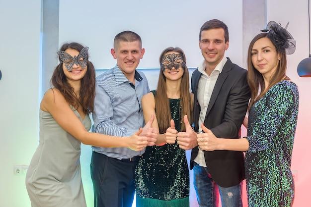 Grupa szczęśliwych przyjaciół w maskach na imprezie sylwestrowej pokazując kciuk do góry