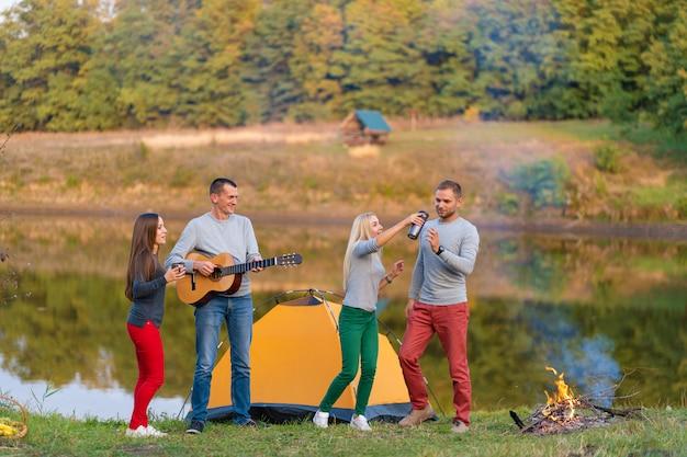 Grupa szczęśliwych przyjaciół z gitarą, zabawy na świeżym powietrzu, tańca i skakania w pobliżu jeziora w tle parku piękne niebo. zabawa na kempingu