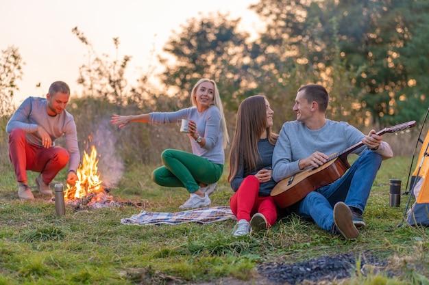 Grupa szczęśliwych przyjaciół z gitarą, zabawy na świeżym powietrzu, w pobliżu ogniska i namiotu turystycznego. zabawa na kempingu szczęśliwa rodzina