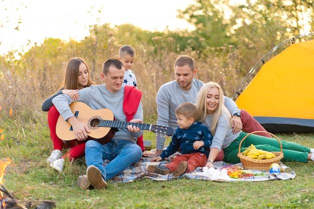 Grupa szczęśliwych przyjaciół z namiotem i napojami grających na gitarze na campingu