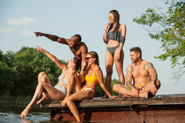 Grupa szczęśliwych przyjaciół, zabawy i śmiechu na molo na rzece.