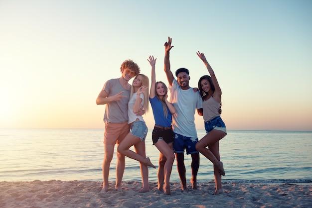 Grupa szczęśliwych przyjaciół, zabawy na plaży oceanu o świcie