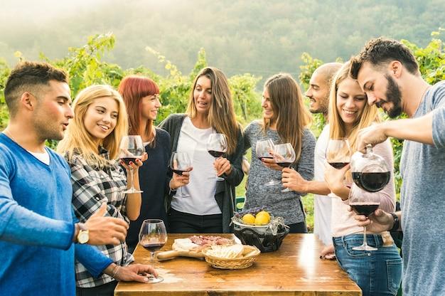 Grupa szczęśliwych przyjaciół, zabawy na świeżym powietrzu, picie czerwonego wina