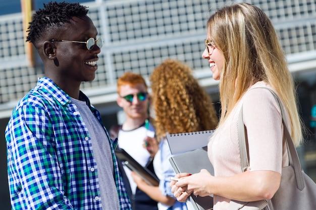 Grupa szczęśliwych studentów młodych mówienia na uniwersytecie.