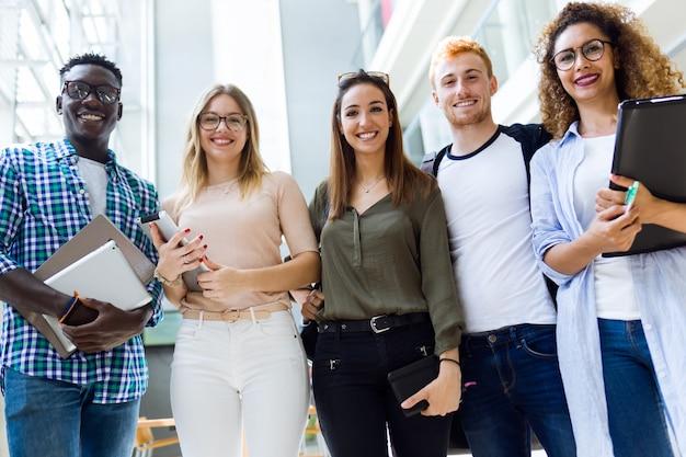 Grupa szczęśliwych studentów młodych spojrzenie na aparat fotograficzny w uniwersytecie.