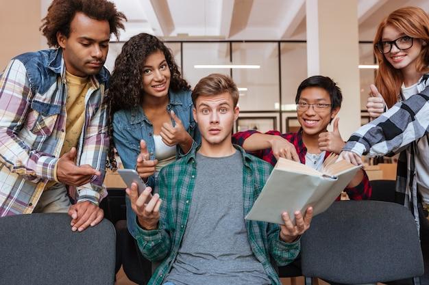Grupa szczęśliwych studentów pokazujących kciuki do góry, stojących wokół zdumionego chłopca z książką i smartfonem