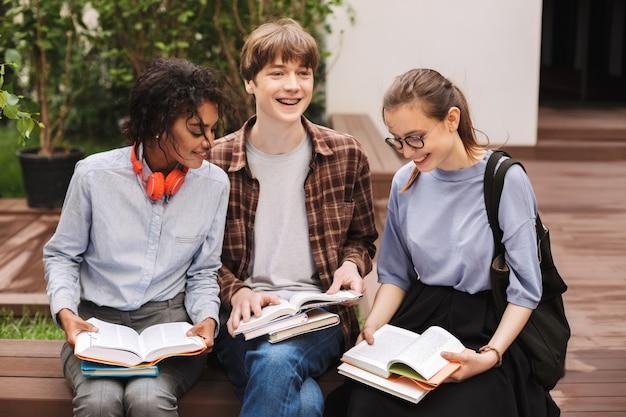 Grupa szczęśliwych studentów siedzi na ławce i czytając książki na dziedzińcu uniwersytetu