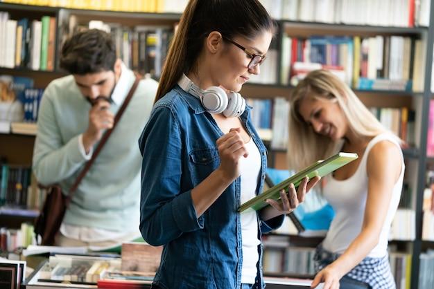 Grupa szczęśliwych studentów studiujących w bibliotece uniwersyteckiej