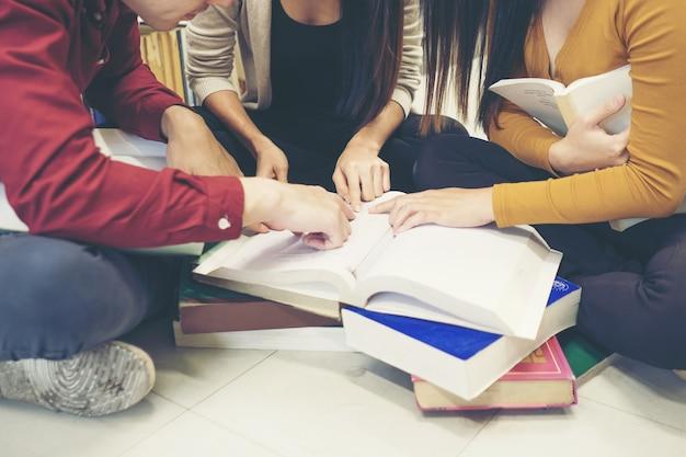Grupa szczęśliwych studentów z książkami mówienia i przygotowywania do egzaminu w bibliotece. koncepcja edukacji.