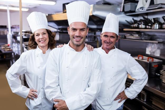 Grupa szczęśliwych szefów kuchni ono uśmiecha się przy kamerą
