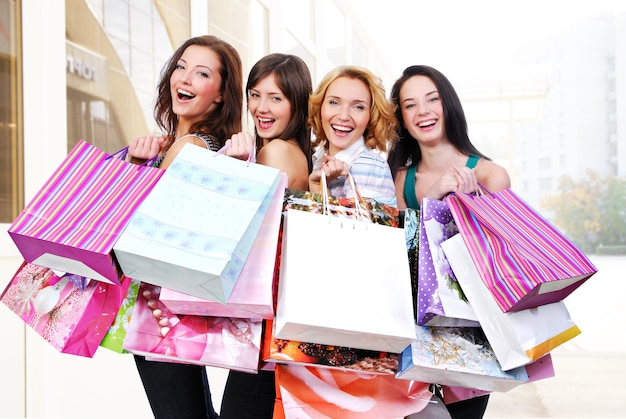 Grupa szczęśliwych uśmiechniętych kobiet robi zakupy z kolorowymi torbami